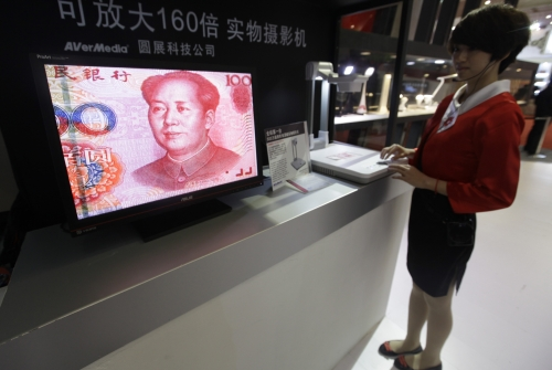 An employee operates a camera to zoom in on the image of a Chinese one-hundred yuan banknote at a production exhibition in Wuhan, Hubei province.