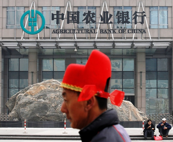 A man wearing a traditional Chinese hat walks past the headquarters of the Agricultural Bank of China in Beijing.