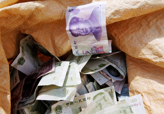 Chinese Yuan bank notes are seen in a vendor's cash sack at a market in Beijing.