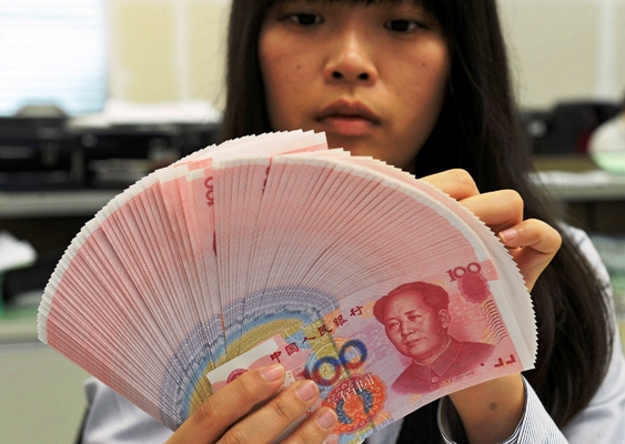An employee counts Chinese yuan notes inside a bank in Taipei.