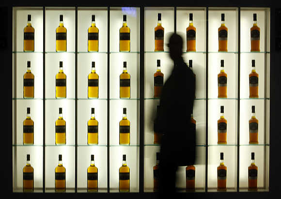 A visitor walks past an alcohol stand during the Tax Free World Association exhibition in Cannes, southeastern France.