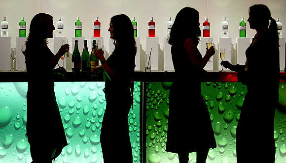Women in silhouette as they drink at a party in a bar in central London.