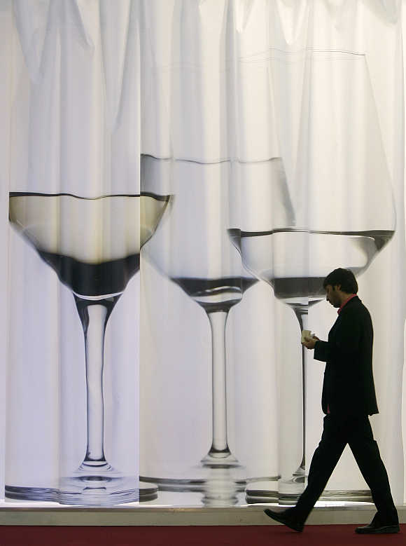 A visitor walks past a wine display at Alimentaria trade show in Barcelona, Spain.