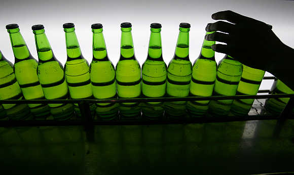 A man picks up a bottle at an assembly line inside the Taiwan Beer factory in Jhunan, Miaoli County.