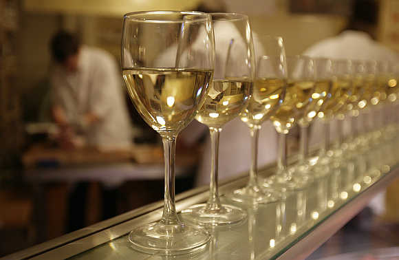 Glasses of white wine are lined up for students to drink at the end of their evening butchery class at the Ginger Pig butchery shop in central London.