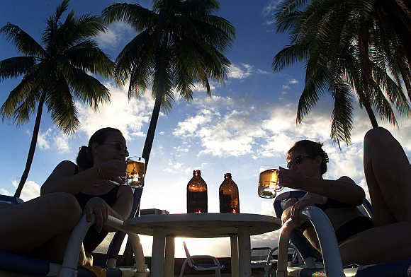 Tourists drink local beer at a beach-side hotel in Suva, Fiji.
