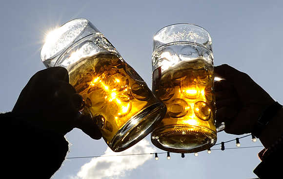 Visitors toast each other on a sunny day during Oktoberfest in Munich, Germany.