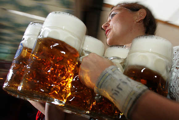 A waitress serves one-litre beer mugs at Munich's Oktoberfest, Germany.
