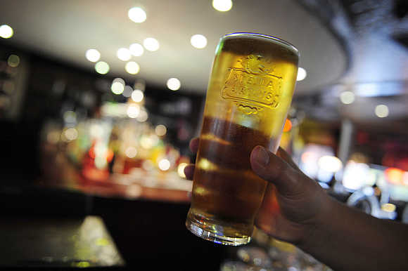 A customer poses for the camera with a pint of beer in a public house in Leeds, northern England.