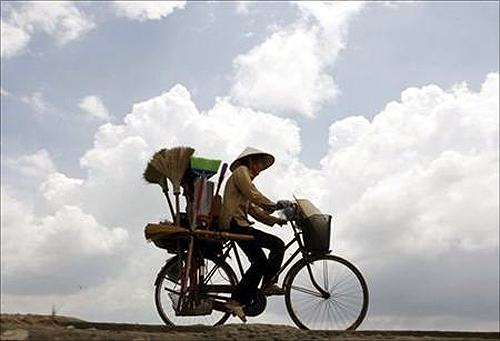 A vendor rides a bicycle on a highway outside Hanoi.