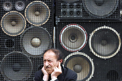 A man protects his ears as he sits in front of loud speakers during an opposition rally in central Yerevan.