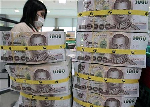 A bank employee counts Thai baht notes at Kasikornbank in Bangkok.