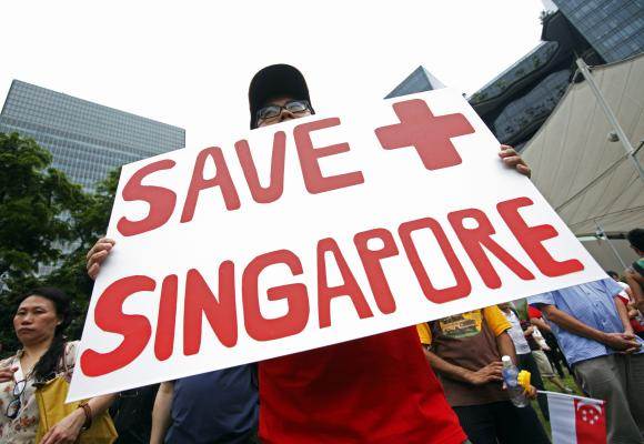 A protester holds a placard during a May Day protest against high living costs and immigration policies at Hong Lim Park in Singapore.