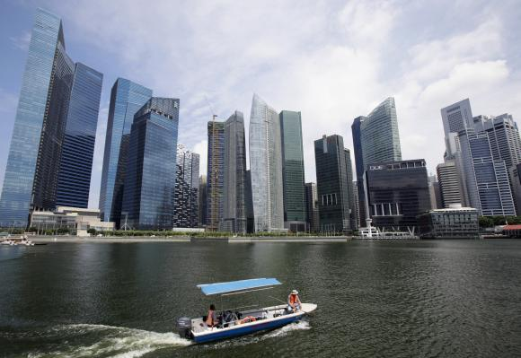 A boat manoeuvres in front of skyscrapers of the Marina Bay Financial Centre in Singapore.