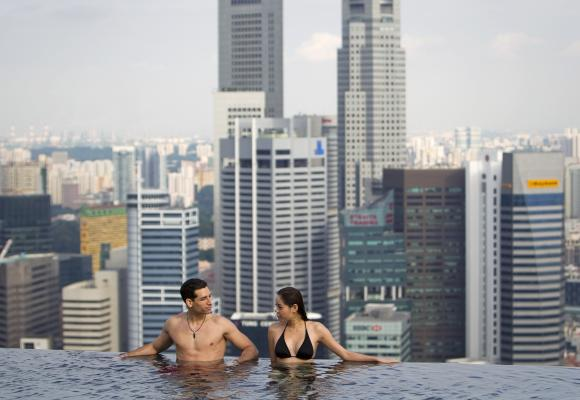 A couple in the infinity pool of the Skypark that tops the Marina Bay Sands hotel towers in Singapore.