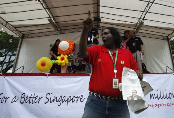 Robertson Fernandez, 61, interrupts speakers during a May Day protest against against high living costs and immigration policies at Hong Lim Park in Singapore.