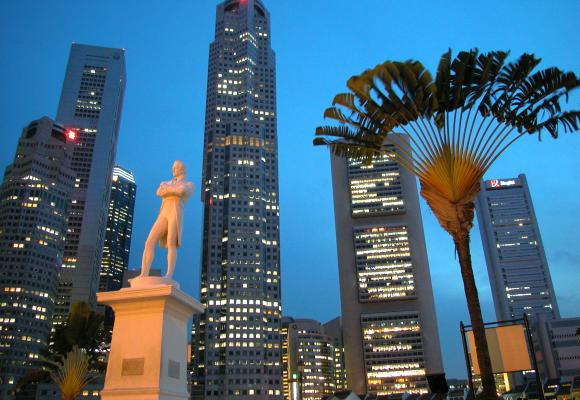 Singapore's skyline rises over a statue of Sir Stamford Raffles.