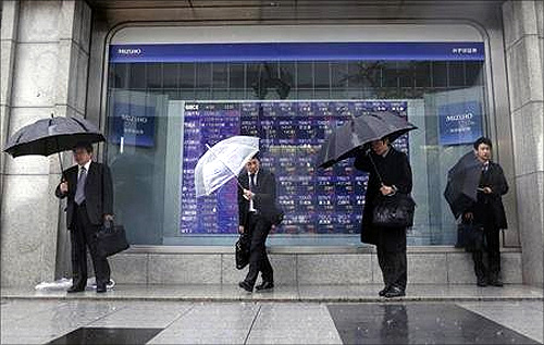 Pedestrians holding umbrellas stand in front of a stock index board showing various stock prices outside a brokerage in Tokyo.