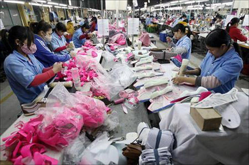 Employees work on an assembly line at a shoe factory in Tan Lap village, outside Hanoi.
