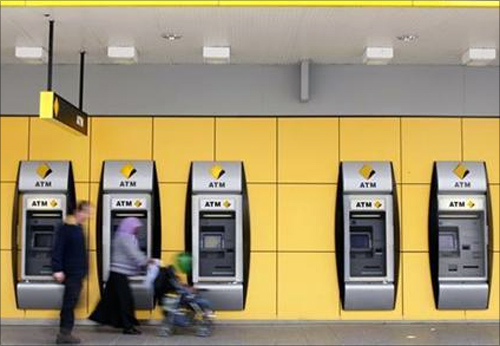 A couple walk past Commonwealth Bank automatic teller machines in Melbourne.