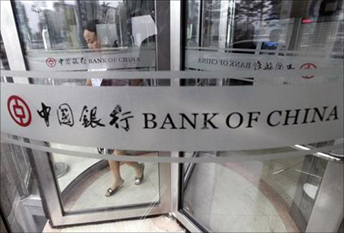 A woman leaves a branch of Bank of China in Beijing.