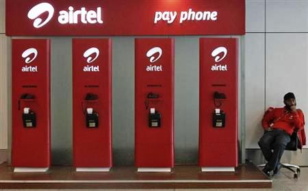 An employee sits at a Bharti Airtel public phone booth installed at the airport in New Delhi.