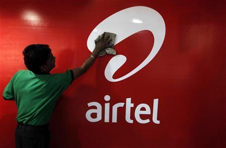 A worker cleans a Bharti Airtel logo inside its shop in Kolkata.