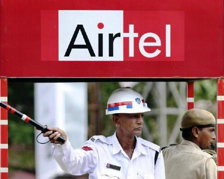 A traffic policeman directs traffic under an advisement of Bharti Airtel at a booth.