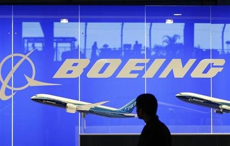 A man looks at a scale model of Boeing's 787 dreamliner at their booth at the Singapore Air Show in Singapore.