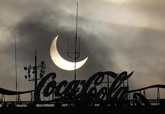A partial solar eclipse is visible behind a Coca-Cola signage.