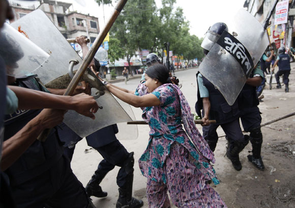 Rahela Akhter, a garment worker, tries to resist beating from the police during a protest.