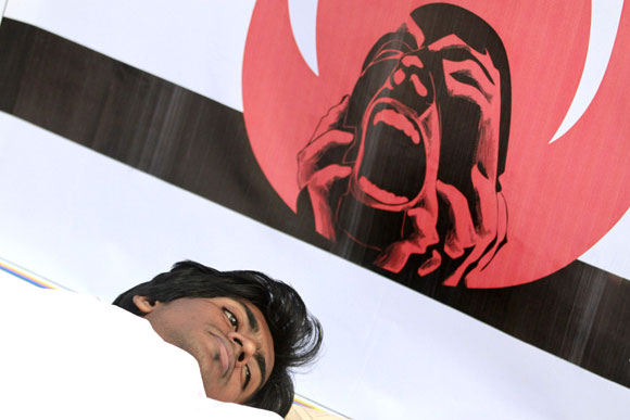 An activist from Magic Movement lies on the ground wearing a traditional Muslim death robe as he takes part in a protest in front of Bangladesh Garment Manufacturers and Exporters Association building in Dhaka.