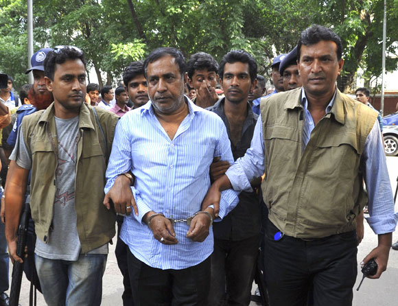 Members of the Detective Branch of Police escort Abdul Khalek, father of Mohammed Sohel Rana, to their custody after his arrest in Dhaka.
