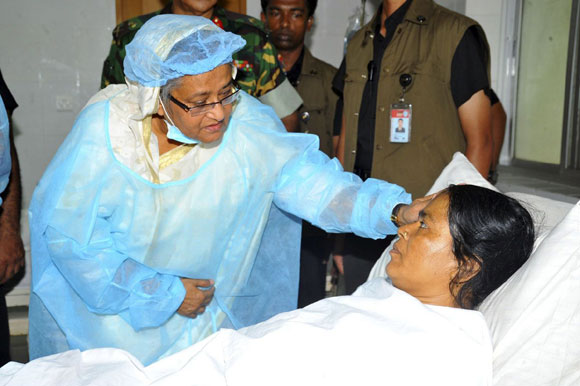 Bangladesh's Prime Minister Sheikh Hasina comforts a garment worker as she visits the survivors of the collapsed Rana Plaza building at a hospital, in Savar.