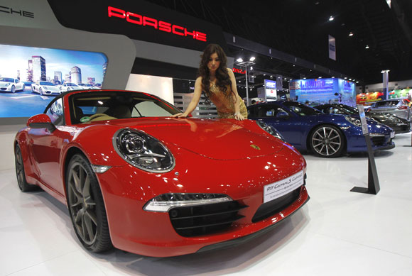 A model poses beside a Porsche 911 Carrera S Cabriolet.