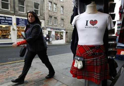 A woman walks past a tourist shop in the Royal Mile in Edinburgh, Scotland.