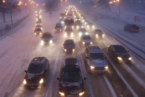 Rush hour traffic crawls as blowing snow batters Lake Shore Drive in Chicago.