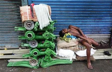 A labourer sleeps beside new iron hand pumps at an iron wholesale market in Kolkata.