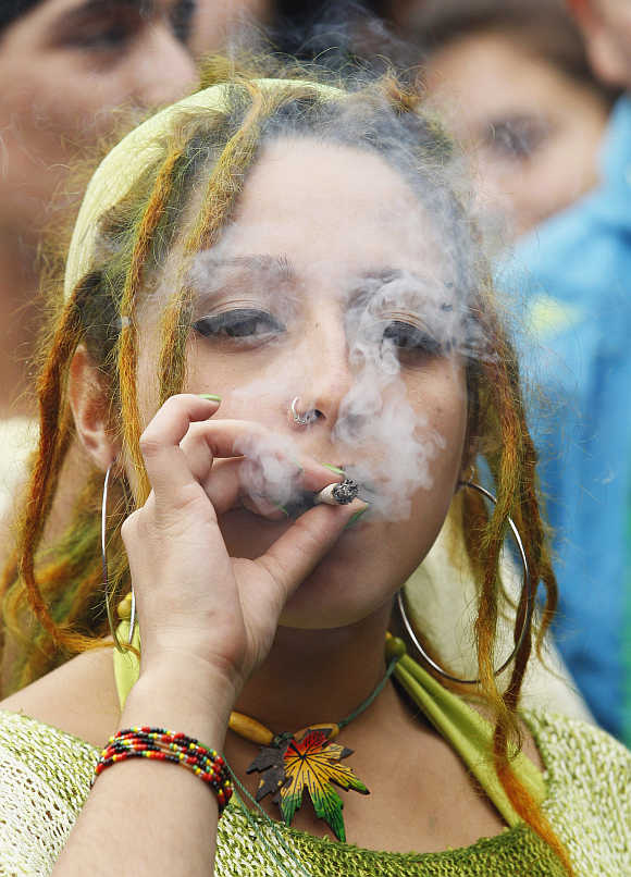 A woman smokes a joint during a rally against drug trafficking and in favour for the legalisation of self-cultivation of marijuana for medicinal and recreational purposes in Valparaiso city, about 121km northwest of Santiago, Chile.