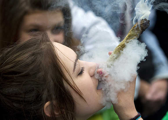 A woman smokes a large marijuana joint at the Vancouver Art Gallery during the annual 4/20 day, which promotes the use of marijuana, in Vancouver, British Columbia, Canada.