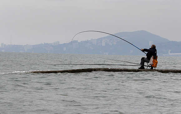 A man fishes in the waters of the Black Sea in Sochi, Russia.