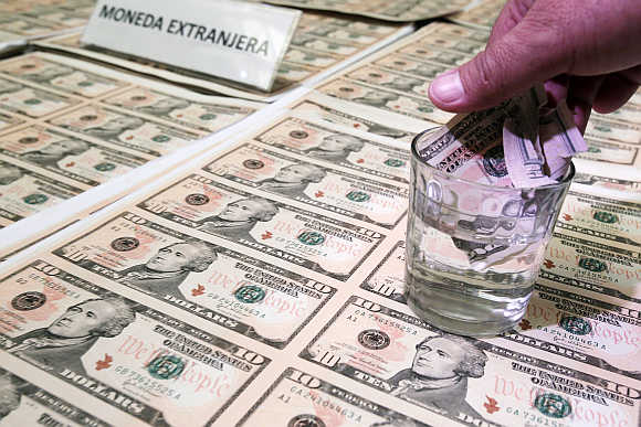 A police officer immerses a counterfeit dollar bill in liquid to show its quality during a media conference in Lima, Peru.