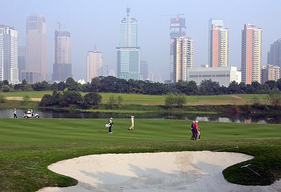 China's top golfer Zhang Lianwei (C) hits on the 14th fairway overlooking the city skyline during the third round of the $1.2 million China Open golf tournament at Shenzhen Golf Club in China's southern city of Shenzhen.