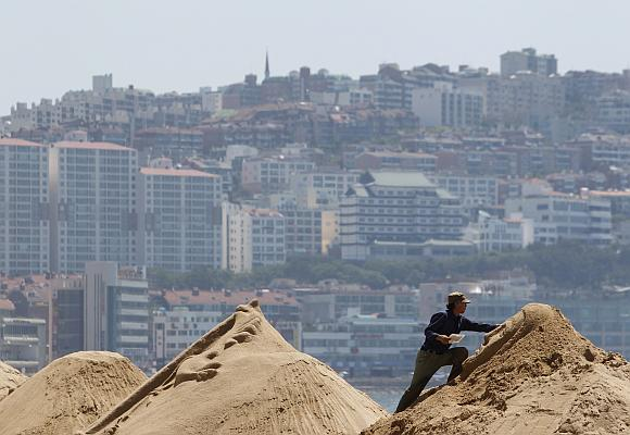 An artist adds finishing touches to a sand sculpture at the upcoming Haeundae Sand Festival in Busan.