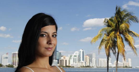 Cuban immigrant Ana Soto poses during a photo session with the Miami skyline in the background.