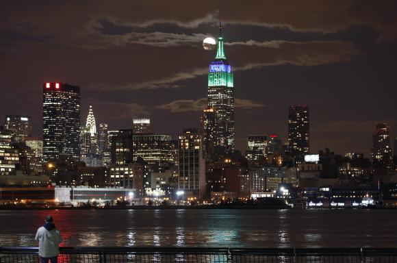 A full moon rises behind the Empire State Building in New York as a man watches in a park along the Hudson River in Hoboken.