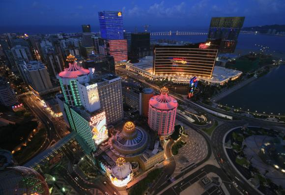 A general view of local and foreign casinos in Macau, including Hotel Lisboa (in pink) and Wynn Macau (with orange lines), in the evening.