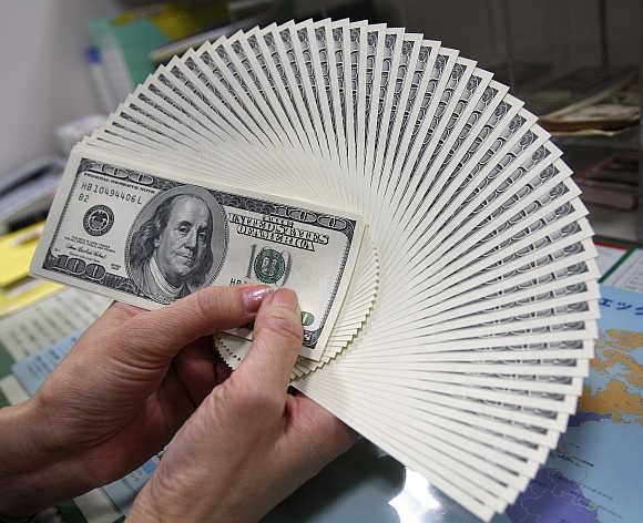 An employee of a money exchange counts US dollar notes in Tokyo, Japan.