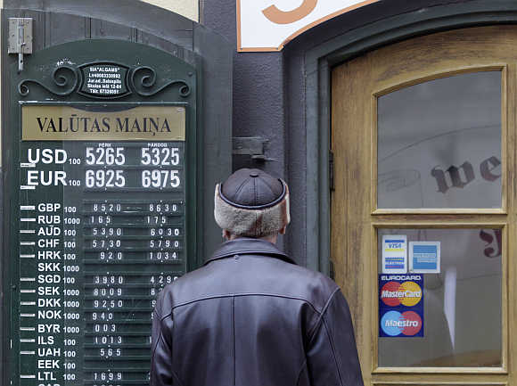 A man looks at currency rates near the exchange office in Riga, Latvia.