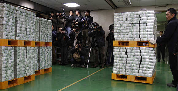 A worker moves stacks of South Korean won for delivery to commercial banks at Bank of Korea's headquarters in Seoul, South Korea.